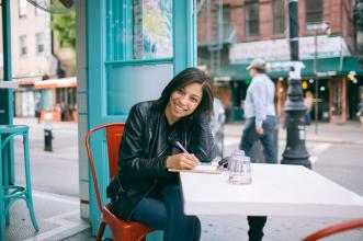 Person smiling and sitting at cafe table with pen in hand