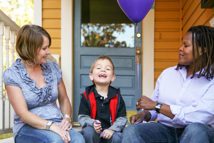 Two adults and a child with a balloon on a porch